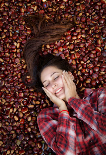 High angle view of woman lying on chestnuts