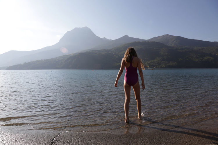Rear view of young woman standing on riverbank against sky