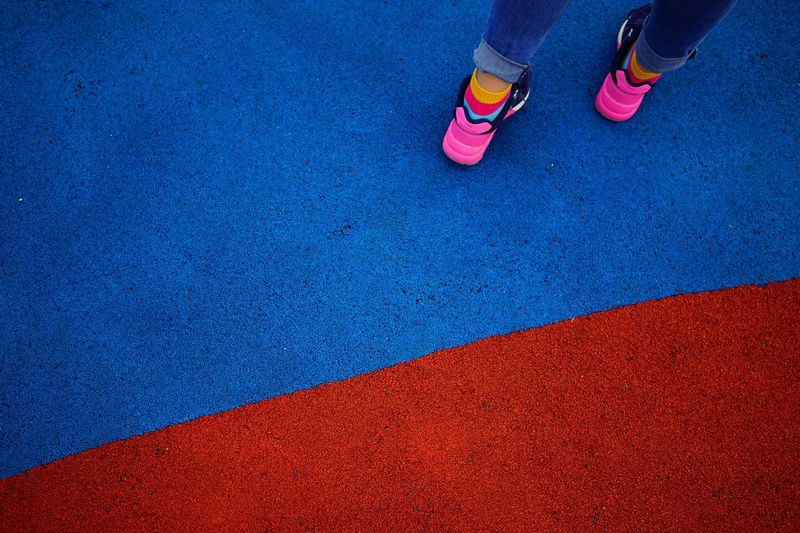 Low Section Of Child Standing On Sports Court