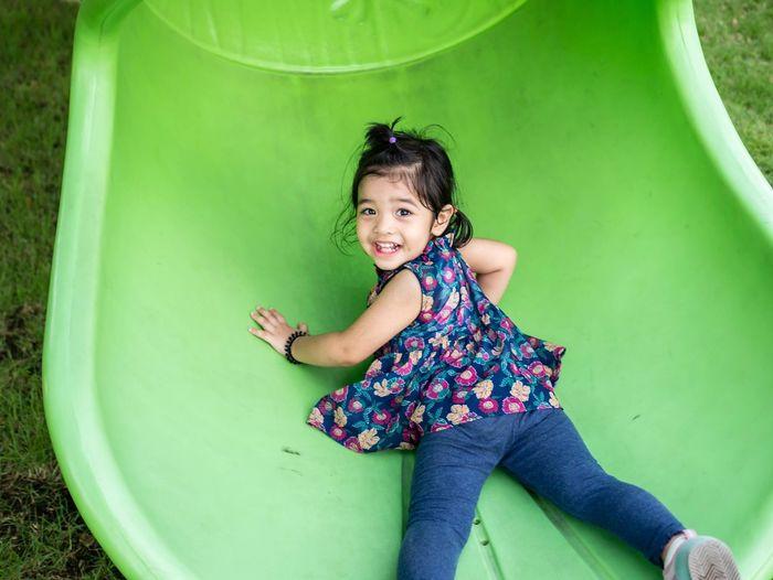 Portrait of smiling girl sliding at park