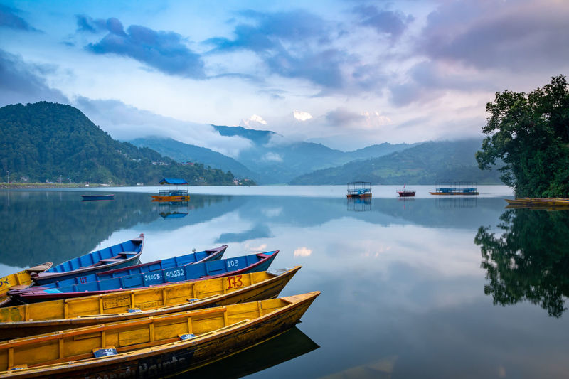 Boats moored in lake against sky