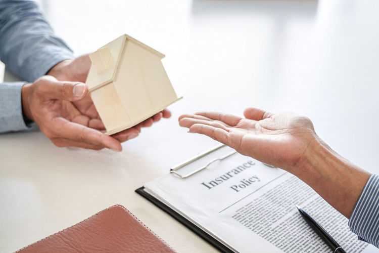 Close-up of hand holding paper with text on table