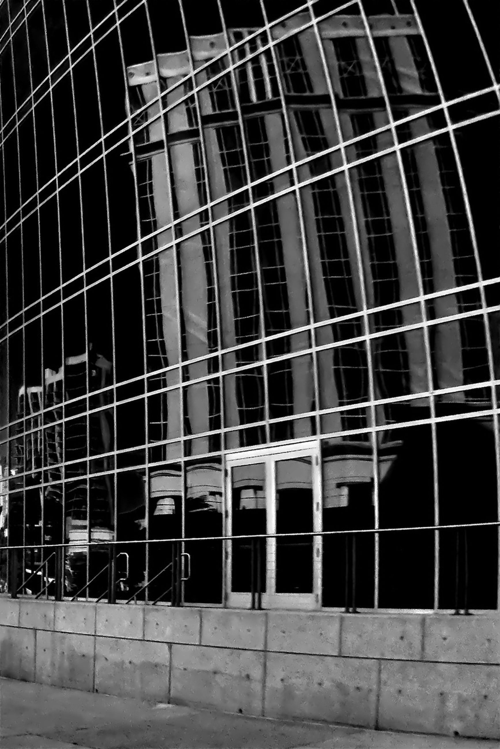 building exterior, architecture, built structure, low angle view, building, window, modern, reflection, glass - material, city, office building, outdoors, no people, day, pattern, metal grate, railing, sunlight, metal