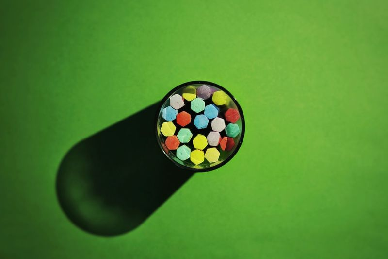 Directly Above View Of Colorful Chalks In Glass With Shadow On Green Background