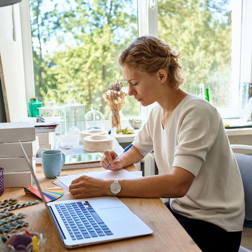 Woman using laptop while sitting on table