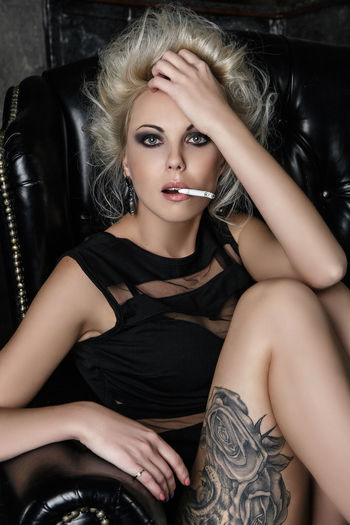 beautiful rock girl with tattoos smoking Beautiful Woman Beauty Blond Hair Cigarette  Fashion Fashion Model Girl With Tattoos Glamour Indoors  Lifestyles Looking At Camera Make-up One Person One Young Woman Only Portrait Rock Rock-n-roll Sitting Smoke Smoking Sofa Tattoo The Portraitist - 2017 EyeEm Awards Young Adult