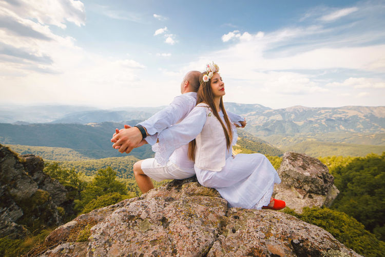 Couple sitting on rock against mountains