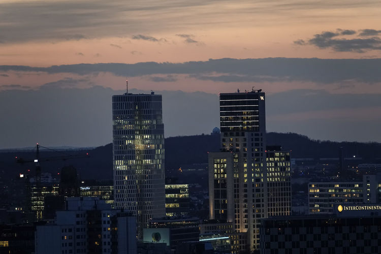 High angle view of illuminated buildings against romantic sky