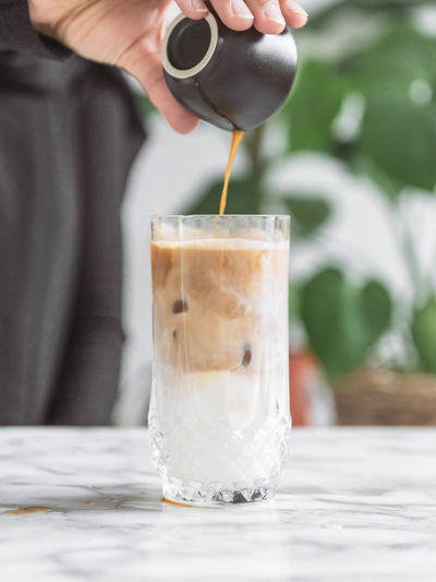 Midsection of person pouring drink in glass