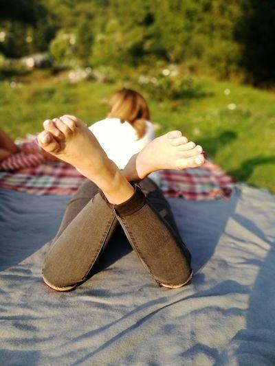 Woman With Legs Crossed Lying On Blanket In Park