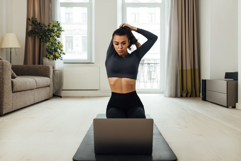 Young woman exercising while looking at laptop