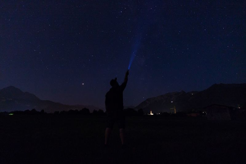 Silhouette man holding flashlight while standing on field against sky at night