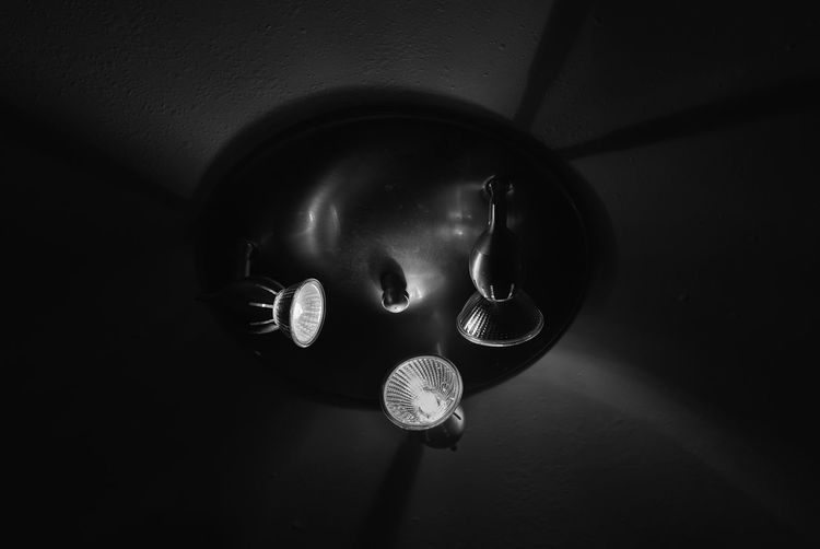 High angle view of illuminated light bulb on wall in darkroom