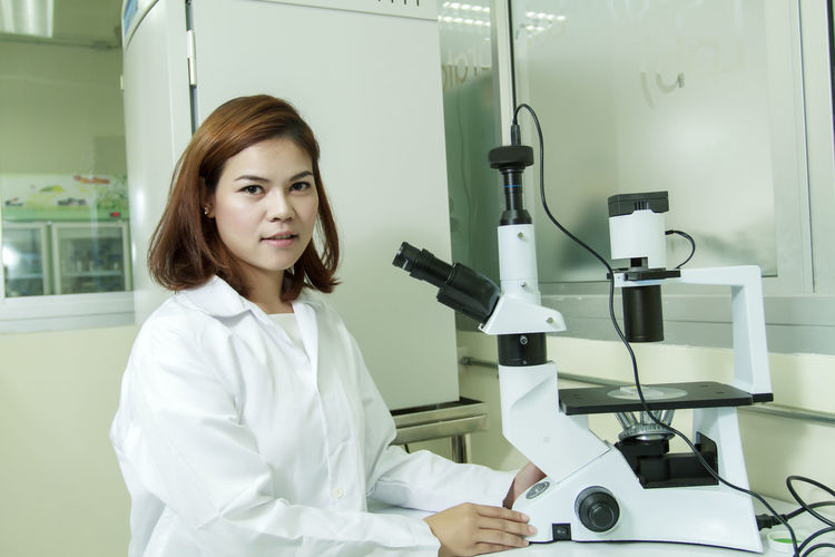 Education Front View Hairstyle Healthcare And Medicine Indoors  Lab Coat Looking At Camera Microscope Occupation One Person Portrait Real People Science Smiling Technology Waist Up Women Young Adult Young Women