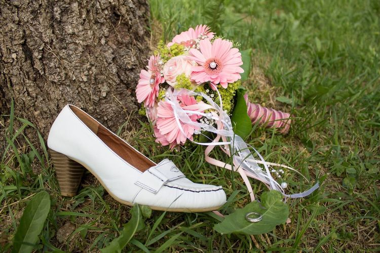 High Angle View Of Abandoned Wedding Shoe And Bouquet On Field