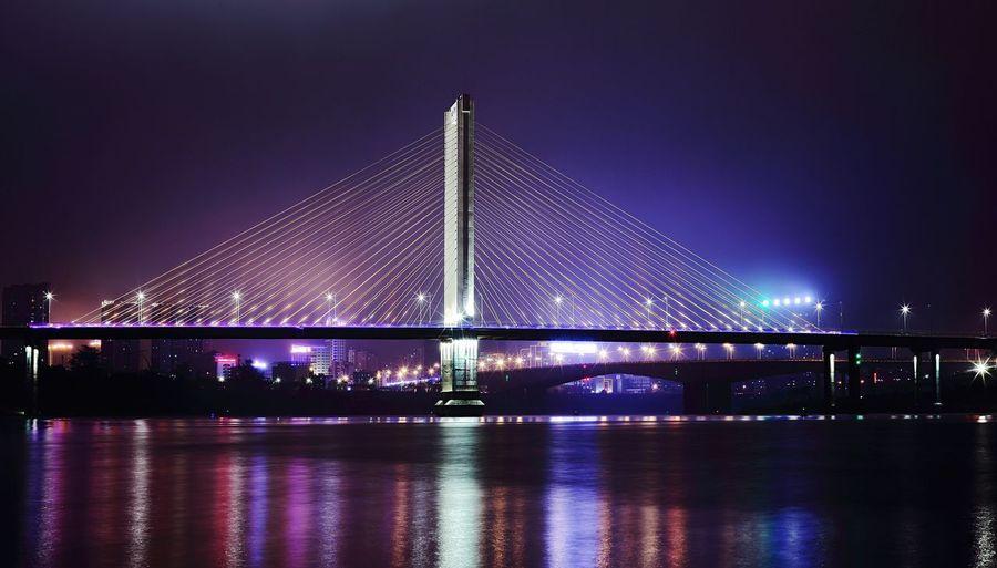 Suspension Bridge With City Lit Up At Night