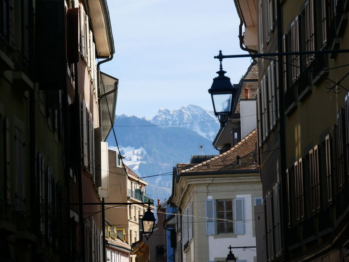 Buildings in city against mountain