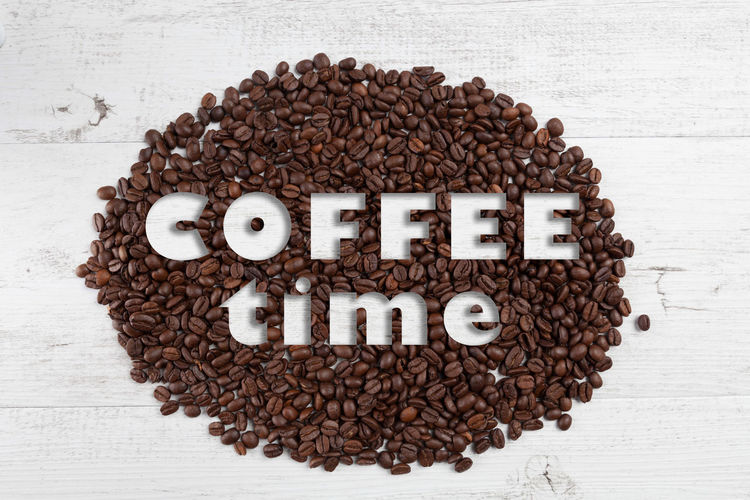 Coffee time text on scattered roasted coffee beans on white rustic wooden background Alphabet Anthropomorphic Face Anthropomorphic Smiley Face Breakfast Brown Close-up Coffee - Drink Coffee Bean Coffee Break Coffee Cup Communication Day Directly Above Food Food And Drink Freshness Indoors  Love No People Roasted Coffee Bean Single Word Studio Shot Text White Background