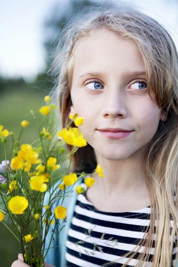 Portrait of teenage girl with yellow flowers