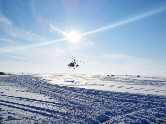 Helicopter Flying Over Snow Covered Landscape Against Sky