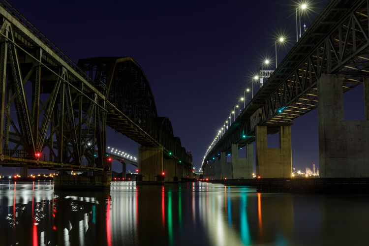 Low angle view of bridge over river at night