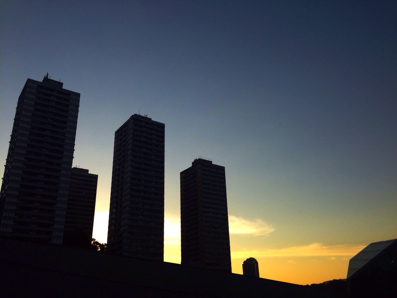 Low Angle View Of Silhouette Buildings Against Blue Sky