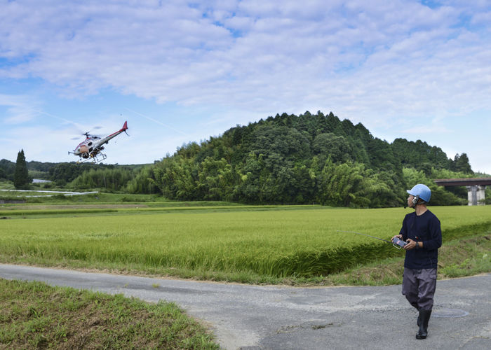 remotely-piloted helicopter-type drone designed to spray crops Adults Only Bamboo Forest Full Length Nature One Person Outdoors People Rice Field Sky Tree