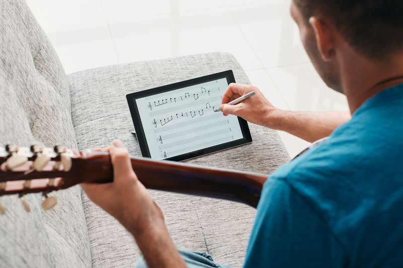 Rear view of man holding guitar writing on digital tablet on sofa at home