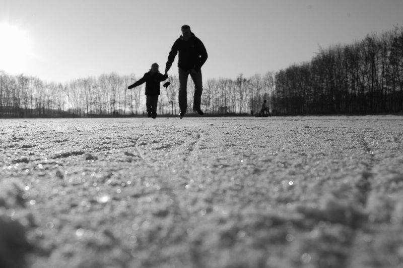 Father and son ice skating against sky