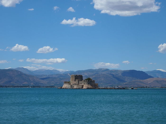 Bourtzi castle amidst sea and mountains against blue sky