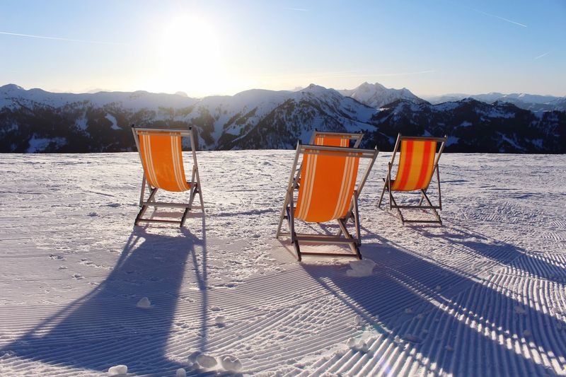 Deck chairs on snowcapped mountain against sky during winter
