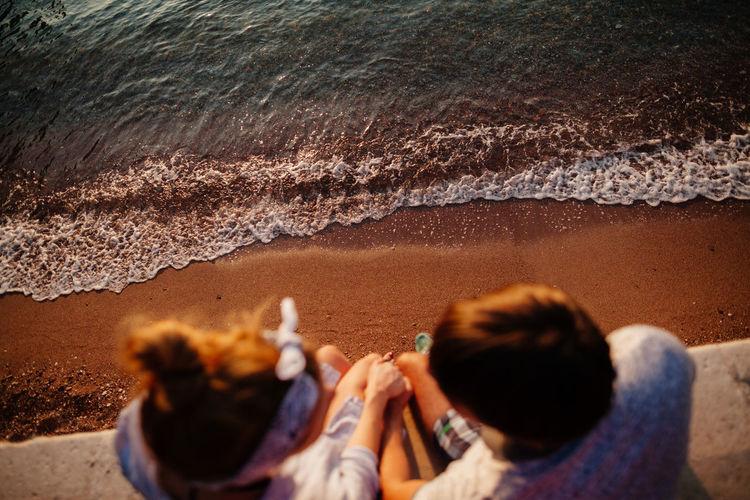 High angle view of couple sitting over sea