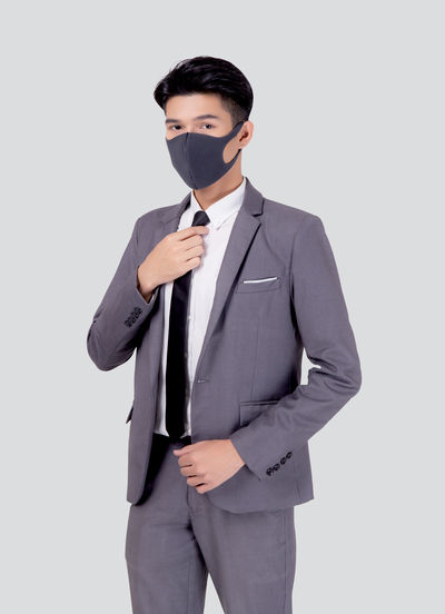 Portrait of young businessman wearing mask against white background