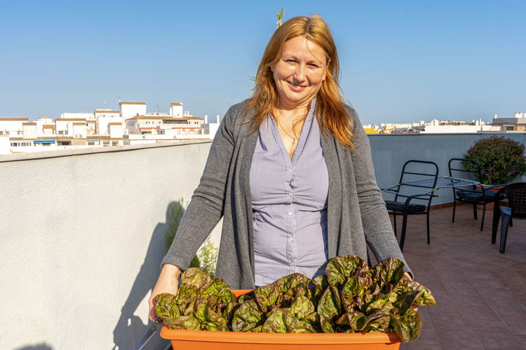 Portrait of smiling woman with vegetables in front of building