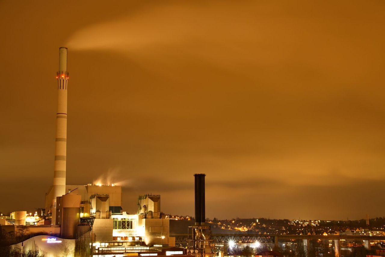 Factory Emitting Smoke Against Orange Sky