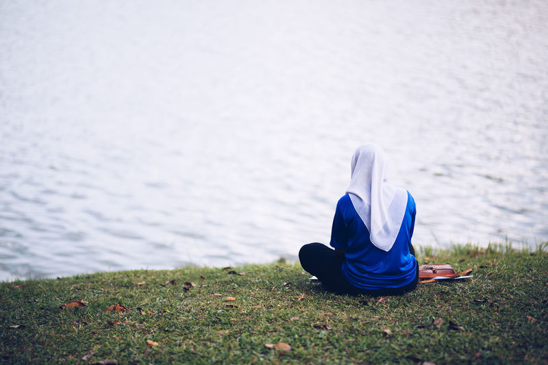 Hood - Clothing Lake Nature One Person Outdoors Real People Sitting Water Women Breathing Space