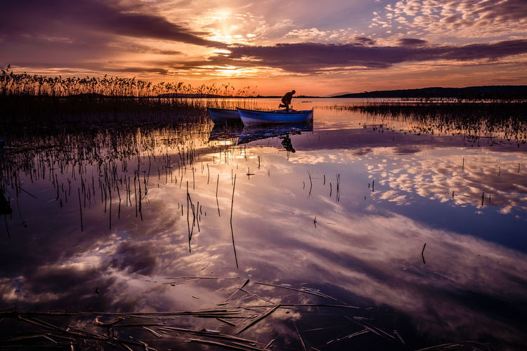 Fisherman under the sunset. Water Nautical Vessel Transportation Sunset Sky Reflection Mode Of Transportation Cloud - Sky Beauty In Nature Scenics - Nature Nature Tranquility Orange Color Tranquil Scene Lake Idyllic No People Non-urban Scene Outdoors