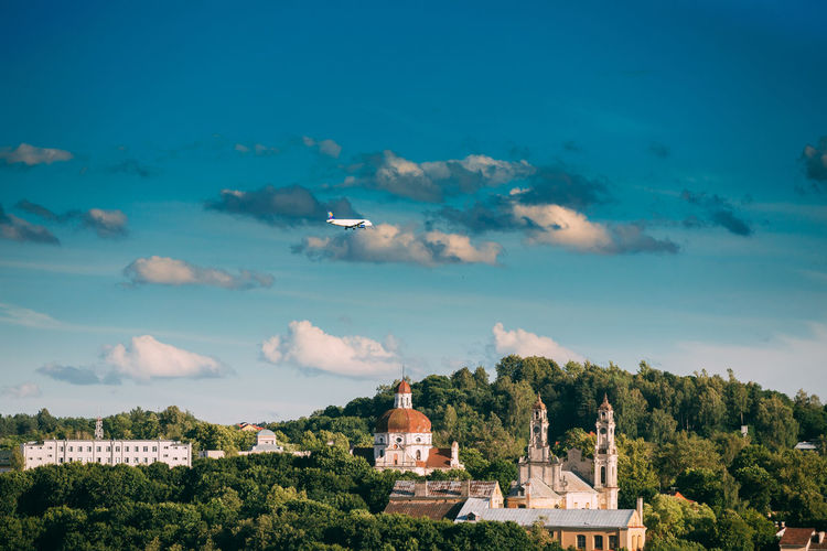 Vilnius, Lithuania. Plane Flying Over Church Of The Ascension And Church Of The Sacred Heart Of Jesus Among Green Foliage. Destination Scenic. UNESCO World Heritage. Famous And Popular Place. Ascension Church Colour Your Horizn Green Lithuania Place Plane Travel Vilnius Architecture Cloud - Sky Day Destination Scenics Europe Flying Foliage Landmark Outdoors Park Sky Temple Tourism Tree Unesco The Traveler - 2018 EyeEm Awards My Best Travel Photo