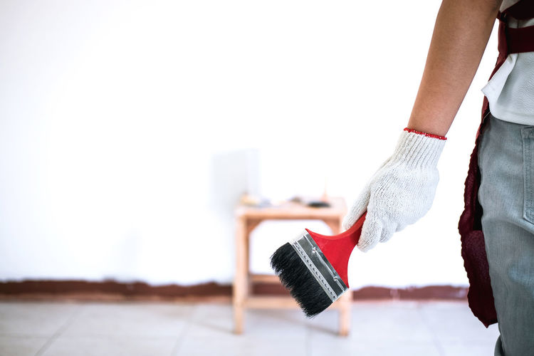 Midsection of painters holding paint brush while painting wall at home