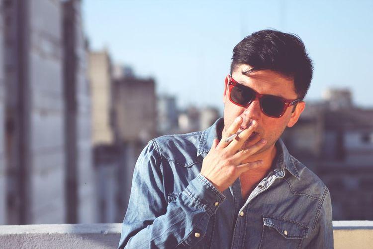 Portrait of man in sunglasses smoking cigarette against buildings