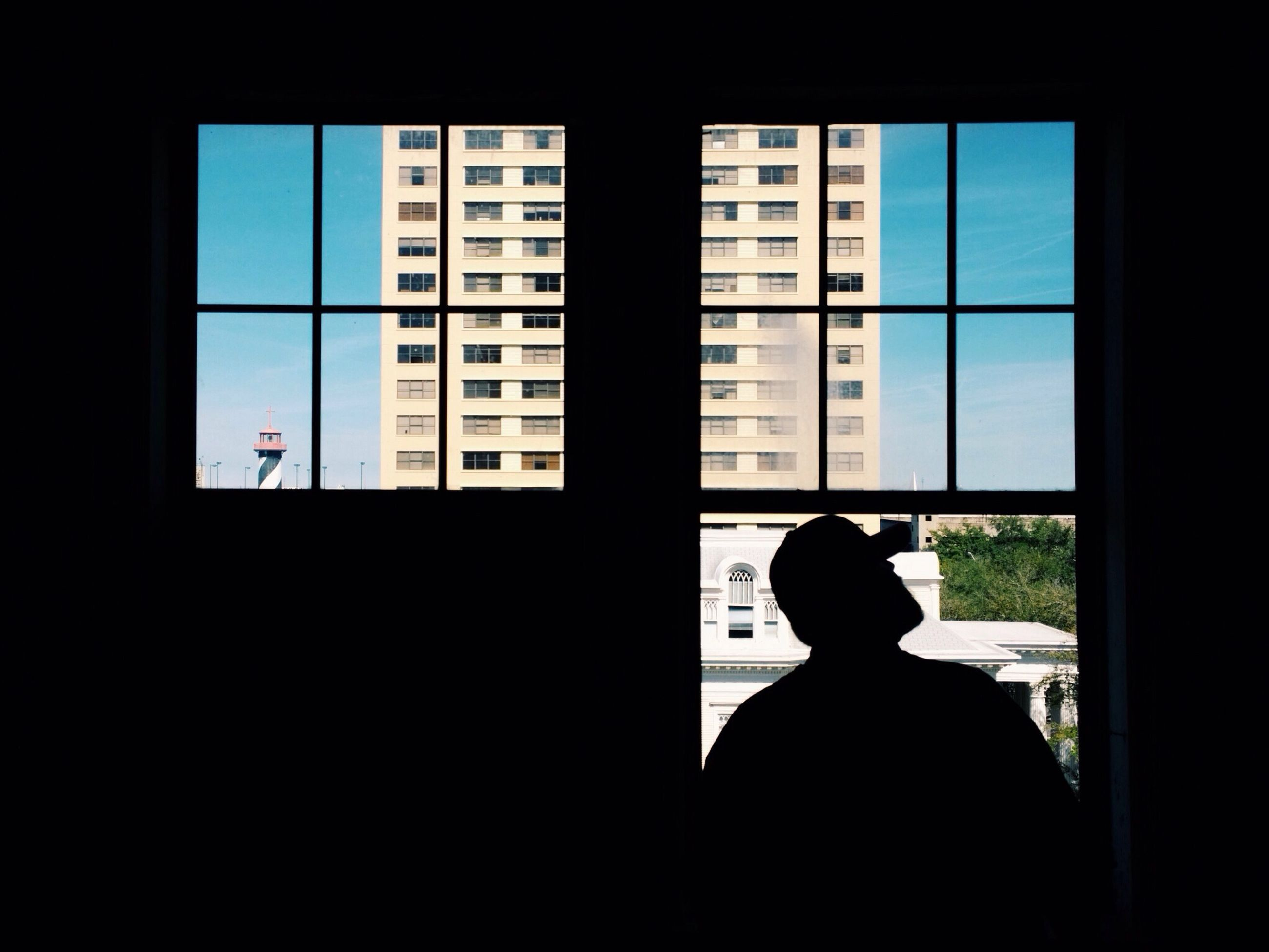 window, indoors, silhouette, glass - material, architecture, transparent, looking through window, built structure, men, building exterior, sitting, dark, city, lifestyles, rear view, home interior, day, glass