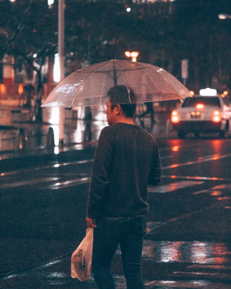 City Full Length Illuminated Leisure Activity Lifestyles Men Night One Person Outdoors Protection Rain Rainy Season Real People Rear View Road Standing Street Under Walking Warm Clothing Water Weather Wet Women Young Adult