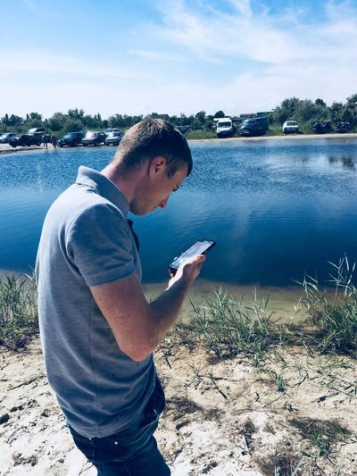 Water One Person Real People Lifestyles Nature Casual Clothing Leisure Activity Communication Young Adult Holding Connection Side View Lake Sky Young Men Day Technology Beach Wireless Technology Outdoors