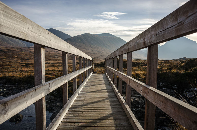 Empty Footbridge Against Mountains