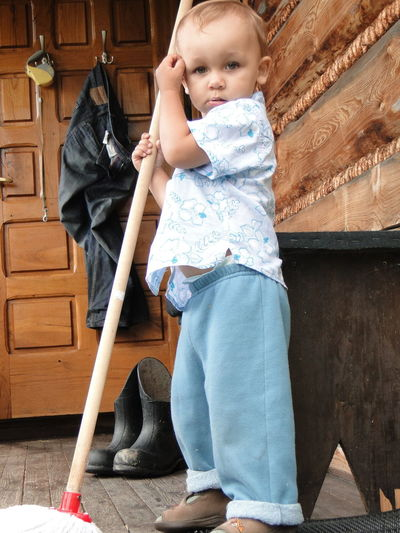 Side view portrait of boy holding mop at home