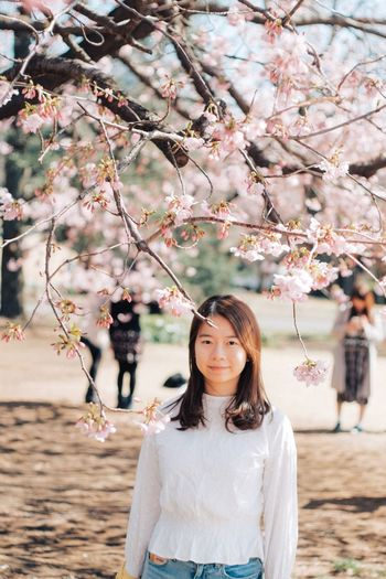 Young woman with cherry blossoms in spring