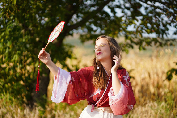 Woman holding hand fan while standing on land
