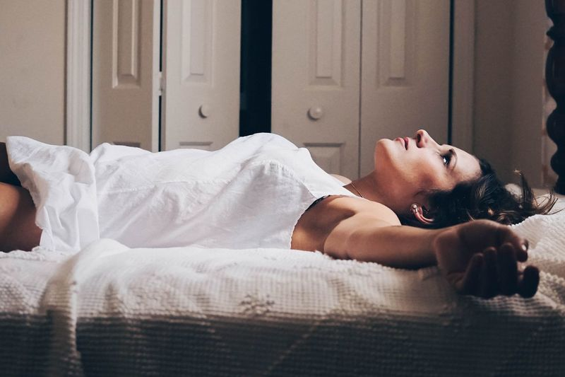 Thoughtful Woman Lying Down On Bed At Home