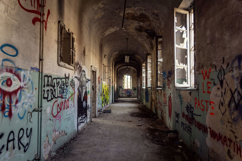 Mental Hospital  Architecture Built Structure Graffiti Building Direction Abandoned The Way Forward Indoors  No People Text Wall - Building Feature Arcade Corridor Old Day Wall Empty Damaged Deterioration Messy Ruined Alley