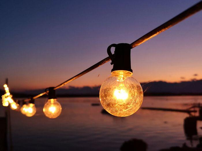 Close-up of illuminated light bulbs against sky at sunset